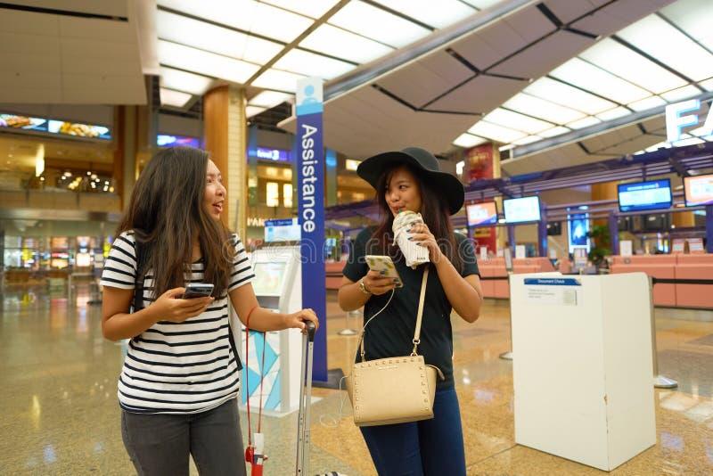 Frauen an der Abfahrthalle Flughafenabfertigungsgebäudes 2 Singapurs Changi stockfotografie