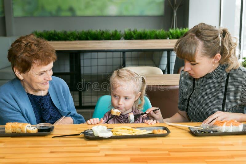 Frauen der gleichen Familie, die in einem Café zu Mittag isst lizenzfreie stockbilder