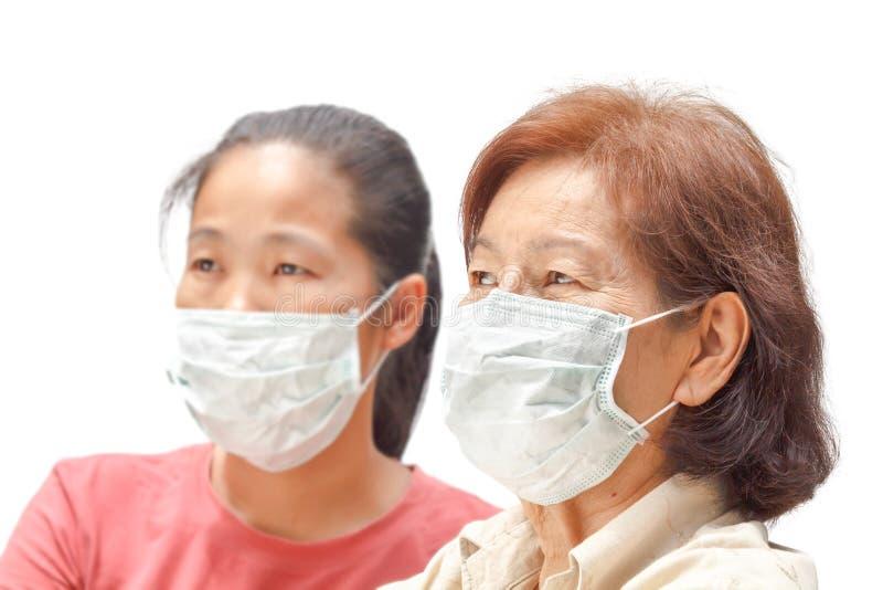Frauen in der schützenden medizinischen Maske stockfotos