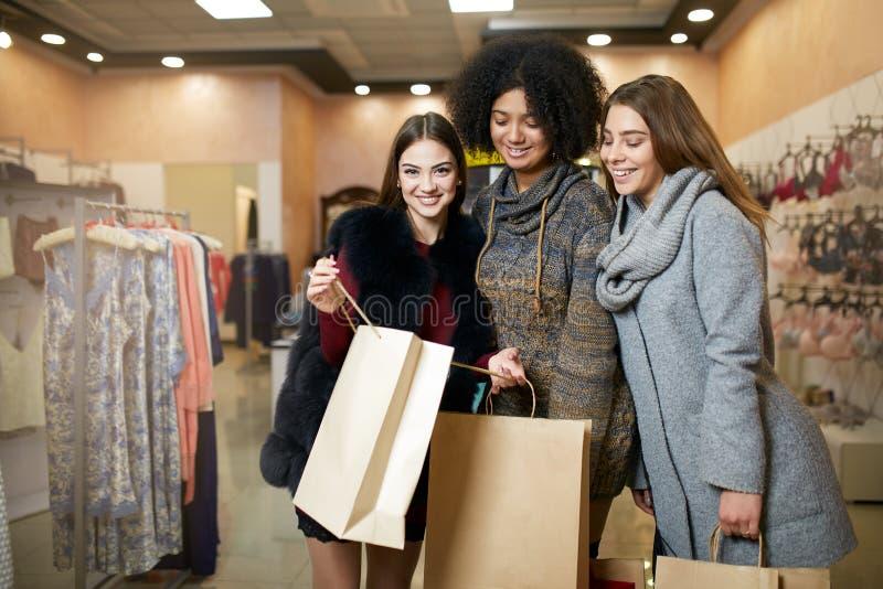 Frauen der verschiedenen Ethnie mit den Einkaufstaschen, die im Bekleidungsgeschäft aufwerfen Porträt von drei lächelnden gemisch stockfotos
