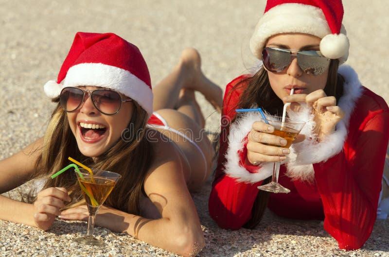 Frauen in der Weihnachtsklage mit Martini auf dem Strand stockbild