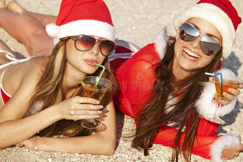 Frauen in der Weihnachtsklage mit Martini auf dem Strand lizenzfreies stockfoto