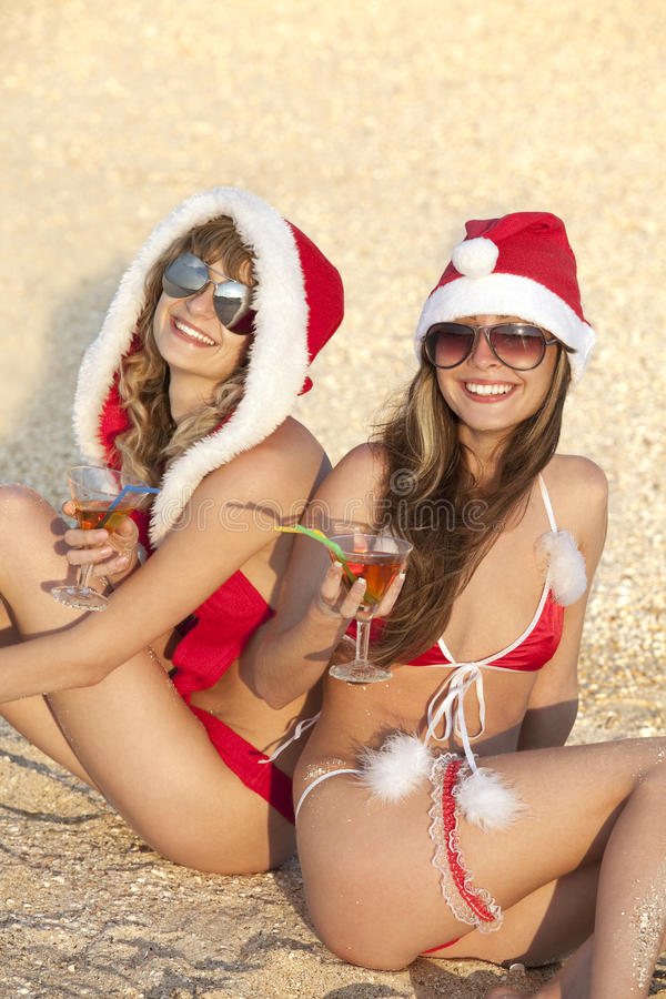Frauen in der Weihnachtsklage mit Martini auf dem Strand stockfotografie