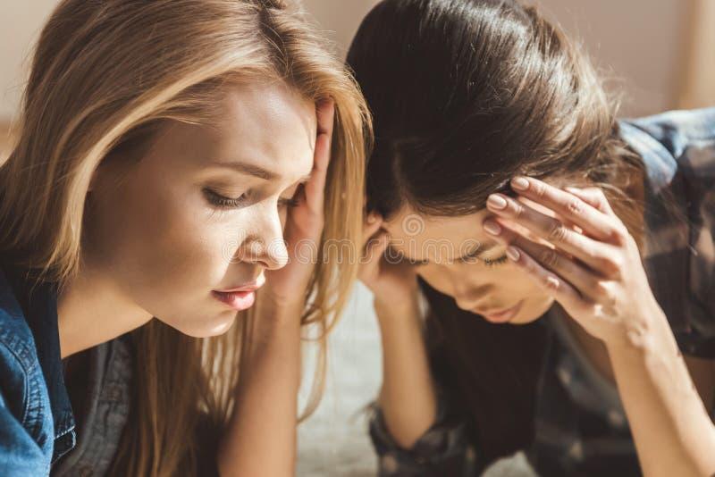 Frauen, die auf Boden mit Kopfschmerzen liegen stockbild