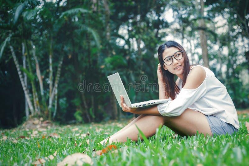 Frauen, die auf dem hölzernen Kasten sitzen und mit Notizbuch arbeiten Sie arbeitend im Park lizenzfreies stockbild