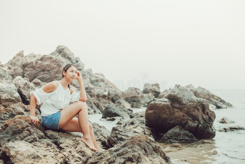 Frauen, die auf dem Stein nahe dem Strand zwischen Reise sitzen stockfotografie