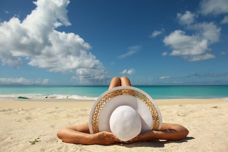 Frauen, die auf dem Strand ein Sonnenbad nehmen lizenzfreie stockfotos