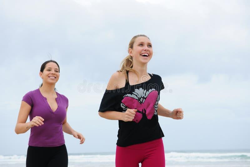 Frauen, die auf den Strand laufen stockfotos