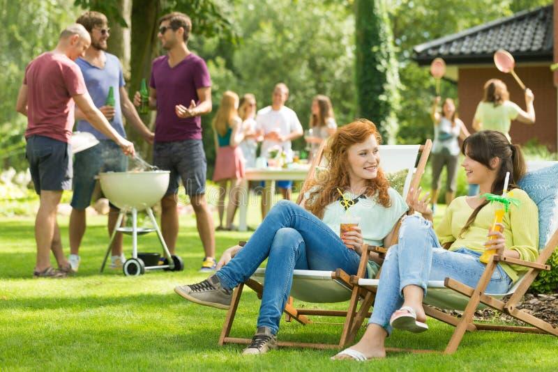 Frauen, die auf einem Gartenfest plaudern lizenzfreie stockfotos