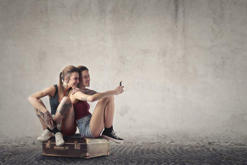Frauen, die auf einer Tasche sitzen lizenzfreies stockfoto