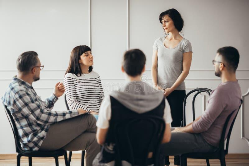 Frauen, die auf pshychologist während der Stützungskonsortiumsitzung hören stockbild