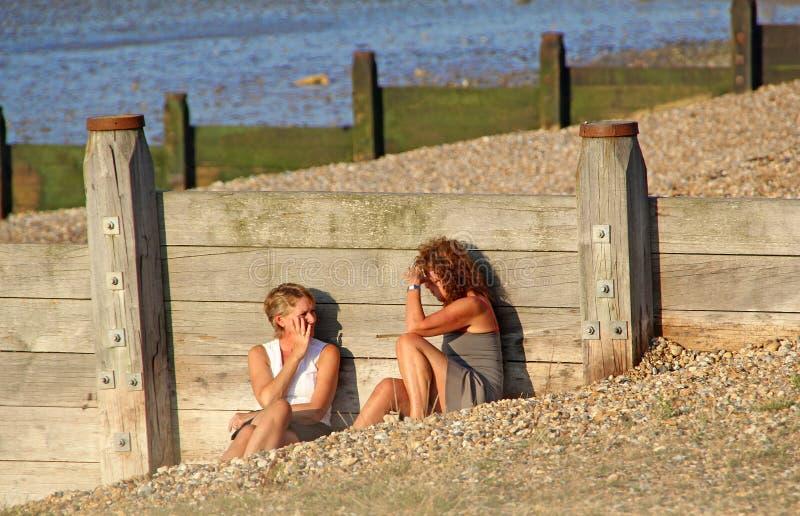 Frauen, die auf Strand nattering sind lizenzfreie stockbilder