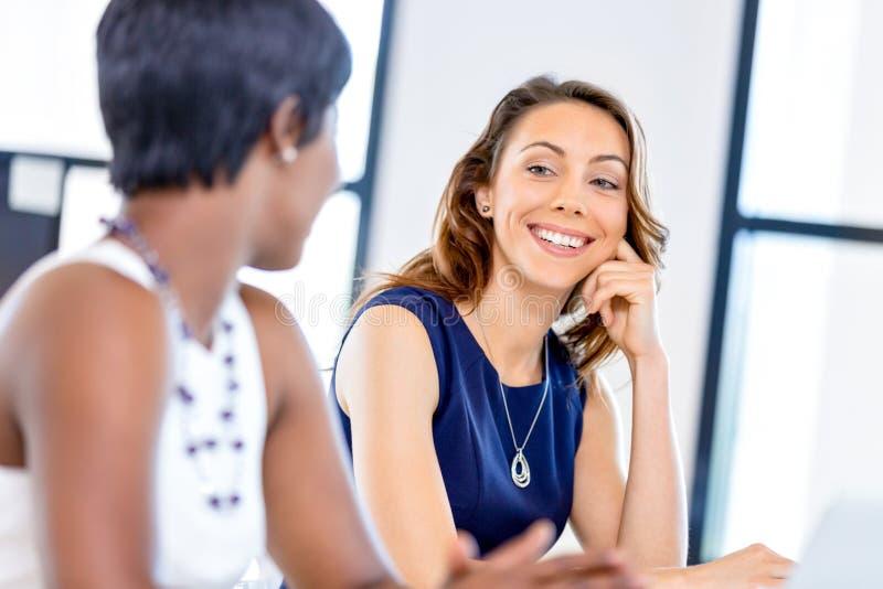 Frauen, die, Büroinnenraum zusammenarbeiten lizenzfreie stockbilder