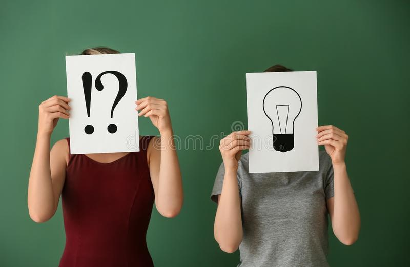 Frauen, die Blätter Papier mit Ausrufs- und Befragungskennzeichen und dem Zeichnen der Glühlampe auf Farbhintergrund halten lizenzfreies stockfoto
