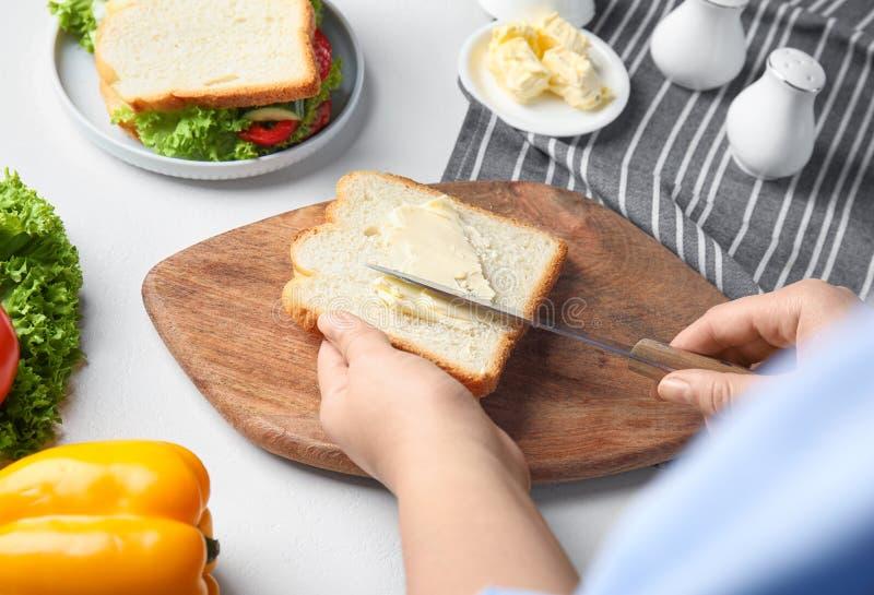 Frauen, die Butter auf Sandwich am weißen Tisch ausbreiten lizenzfreies stockfoto
