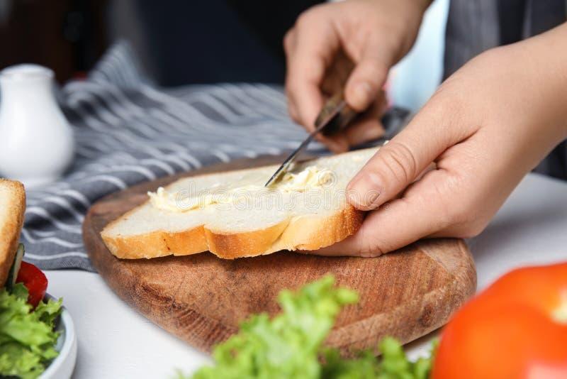 Frauen, die Butter auf Sandwich am weißen Tisch ausbreiten lizenzfreie stockbilder