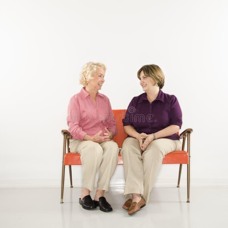 Frauen, die das Unterhalten sitzen. lizenzfreie stockbilder