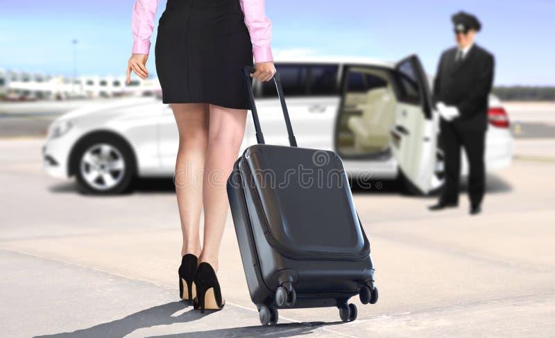 Frauen, die den Koffer verlässt den Flughafen mit weißer Limousine ziehen stockbilder