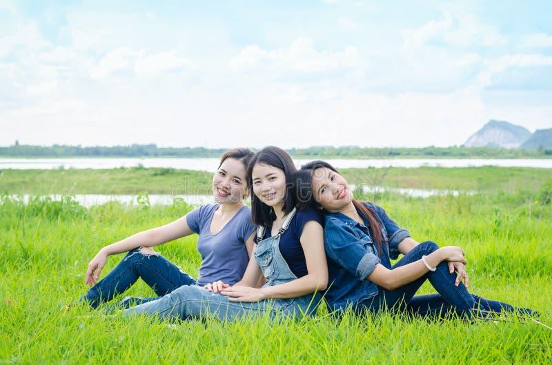 Frauen, die in der Wiese und im Lächeln sitzen stockbilder