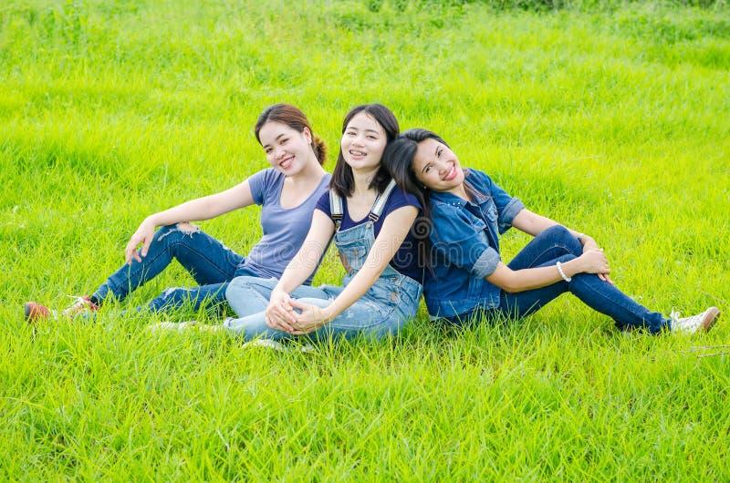 Frauen, die in der Wiese und im Lächeln sitzen stockbild