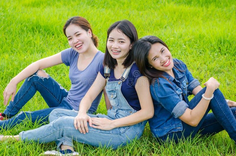 Frauen, die in der Wiese und im Lächeln sitzen stockfotos