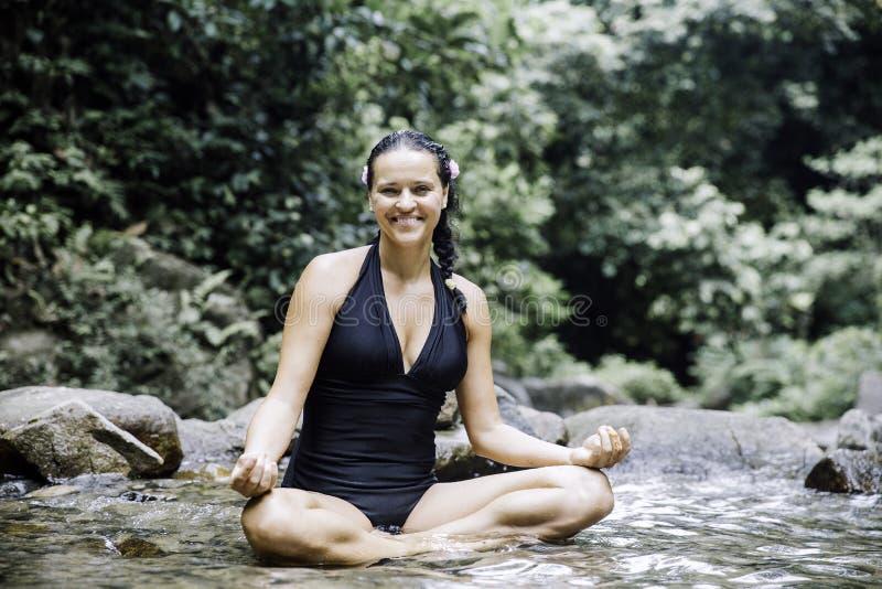 Frauen, die draußen im grünen Park auf Naturhintergrund meditieren lizenzfreies stockfoto