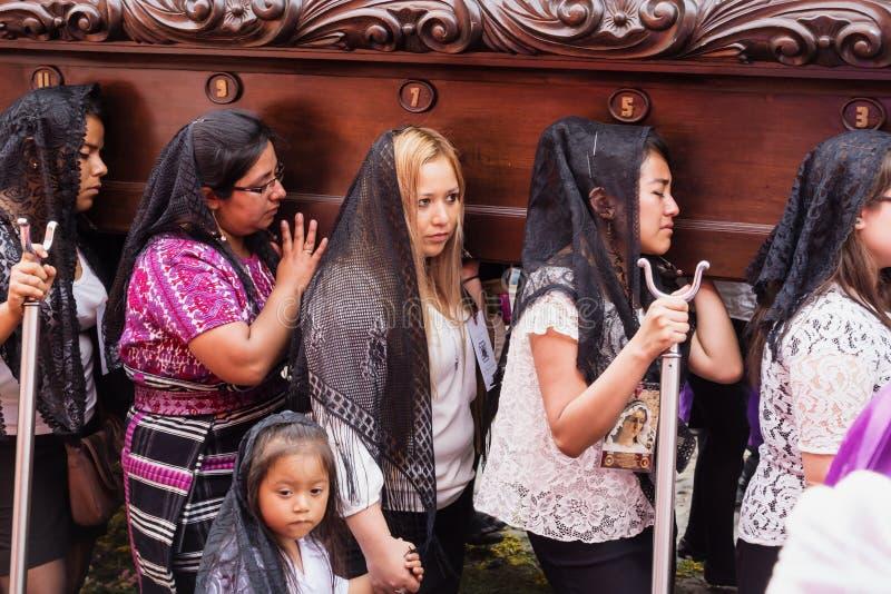 Frauen, die ein Floss an der Prozession von San Bartolome de Becerra, Antigua, Guatemala tragend leiden stockfotografie