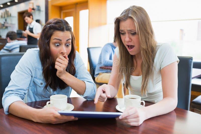 Frauen, die eine Tablette halten und überrascht schauen lizenzfreies stockfoto