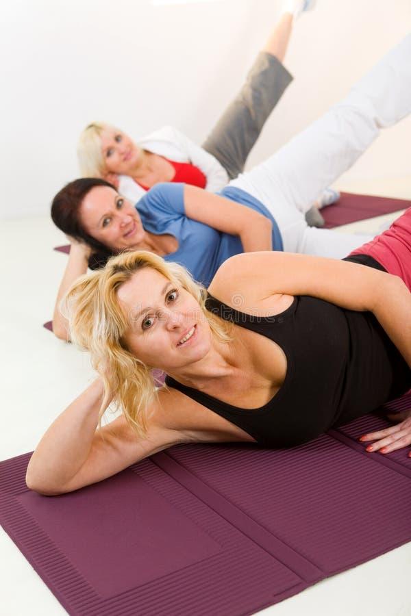Frauen, die exercices auf Matte tun lizenzfreie stockbilder