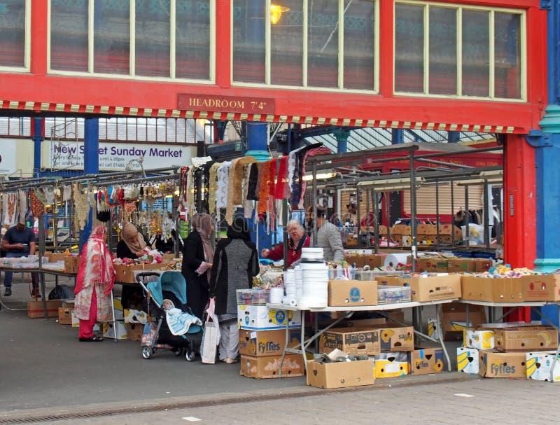 Frauen, die für Gewebe und nähende Materialien auf einem Stall in Huddersfield-Markt in West Yorkshire kaufen lizenzfreie stockfotografie