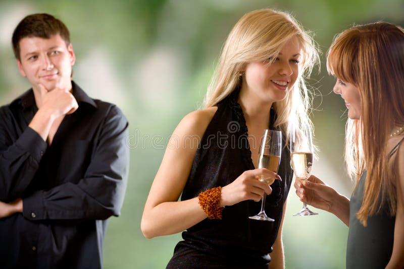Frauen, die Gläser mit Champagner und Lachen und junger Mann anhalten stockfotografie