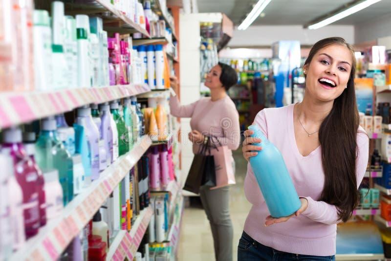Frauen, die Haarpflege im Speicher vorwählen lizenzfreie stockfotos