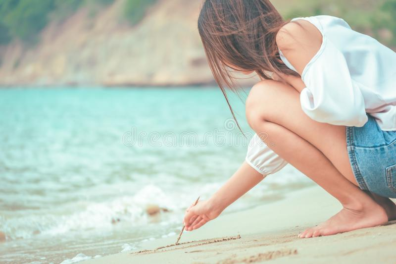 Frauen, die Herz auf Sand auf dem Strand schreiben stockfoto