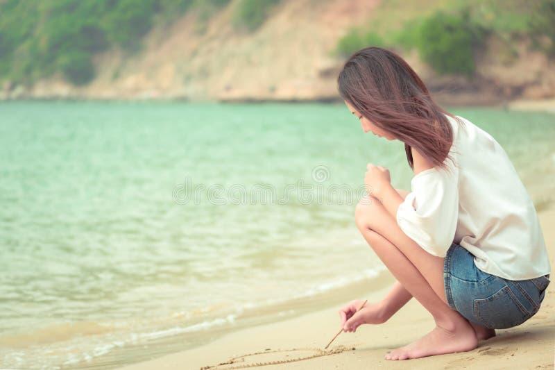 Frauen, die Herz auf Sand auf dem Strand schreiben lizenzfreie stockbilder