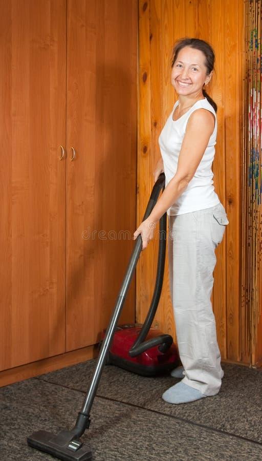 Frauen, die ihr Wohnzimmer säubern stockbilder