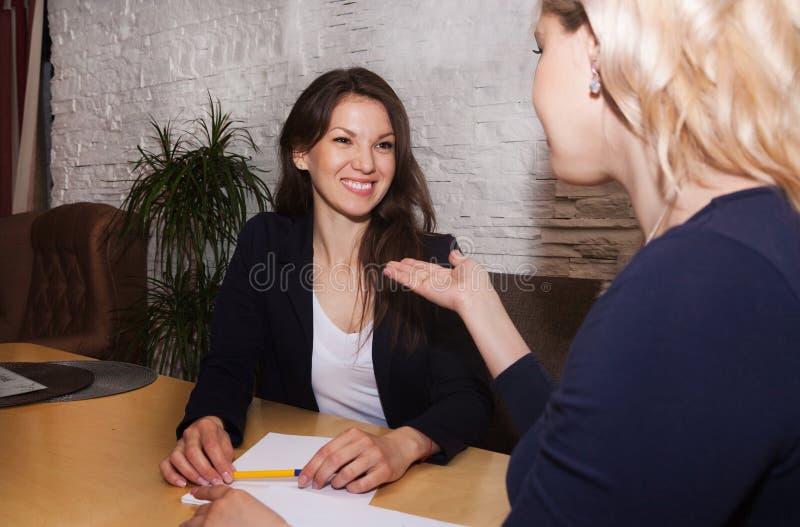 Frauen, die im Büro sprechen lizenzfreie stockfotografie
