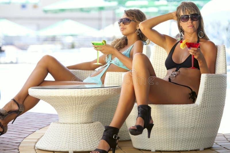 Frauen, die im Stab mit Gläsern von Martini genießen stockbilder