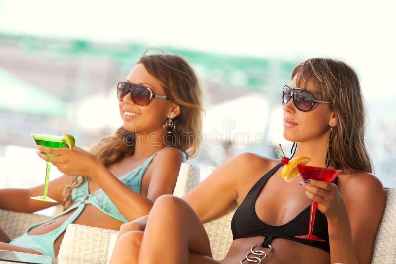 Frauen, die im Stab mit Gläsern von Martini genießen lizenzfreie stockfotos