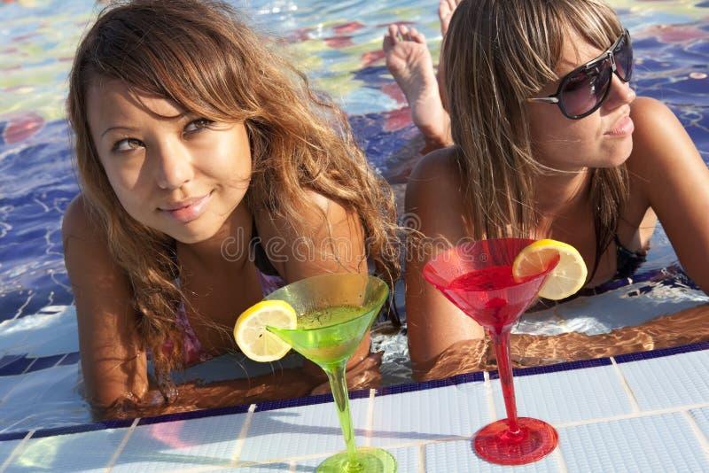 Frauen, die im Swimmingpool genießen lizenzfreies stockfoto