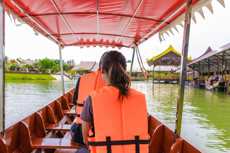 Frauen, die im Transportboot und Schwimmweste tragen sitzen lizenzfreies stockfoto