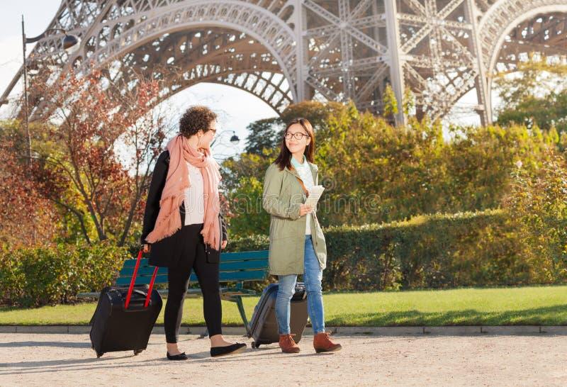 Frauen, die Koffer entlang der Straße von Paris ziehen stockfotos