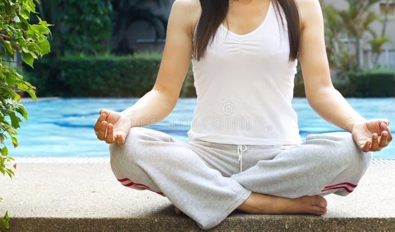 Frauen, die Meditation auf Swimmingpoolhintergrund stationieren stockbild