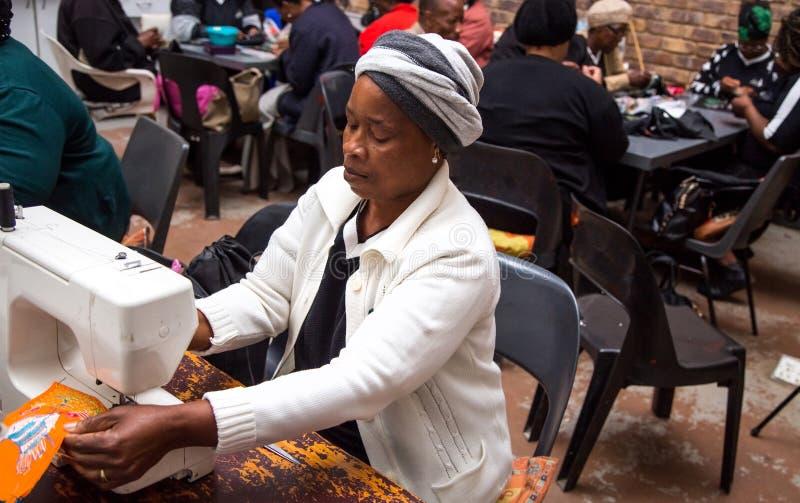 Frauen, die mit einer Nähmaschine säen stockfoto