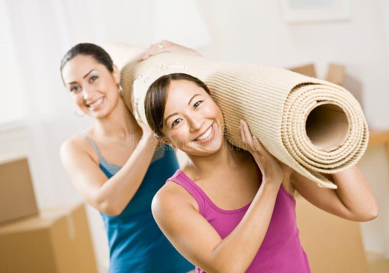 Frauen, die in neues Haus und in tragende Unebenheit umziehen stockbilder