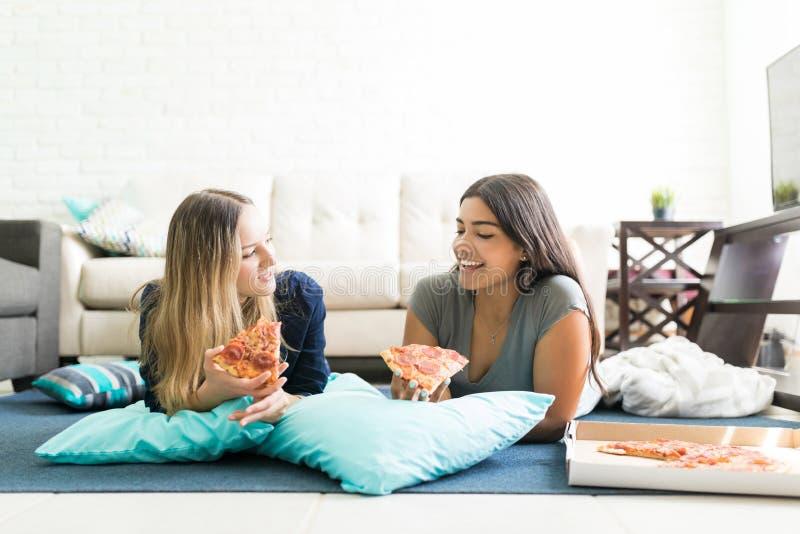 Frauen, die Pizza-Scheiben beim Lügen auf Boden während der Partei halten lizenzfreie stockfotos