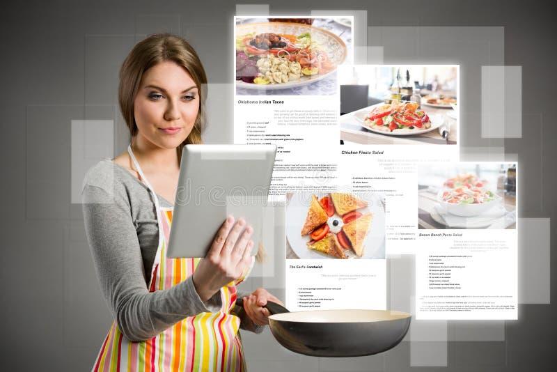Frauen, die Rezepte über dem Internet schauen lizenzfreies stockbild