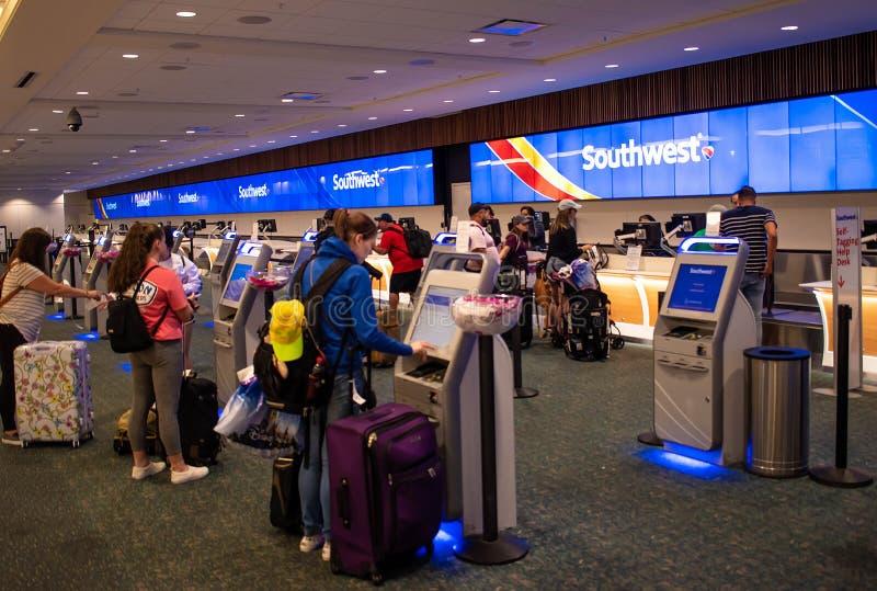 Frauen, die Selbstmaschine im Südwestzähler bei Orlando International Airport verwenden 2 lizenzfreie stockbilder