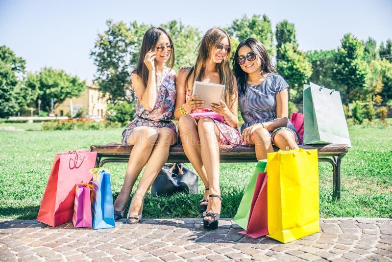 Frauen, die Tablette kaufen und betrachten stockfotos