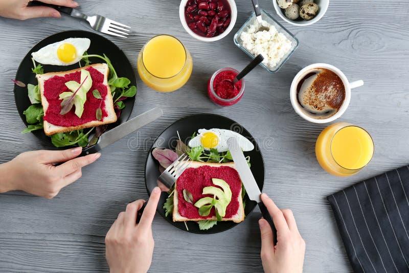 Frauen, die Toast mit Paste und Avocado der roten Rübe essen lizenzfreie stockfotografie