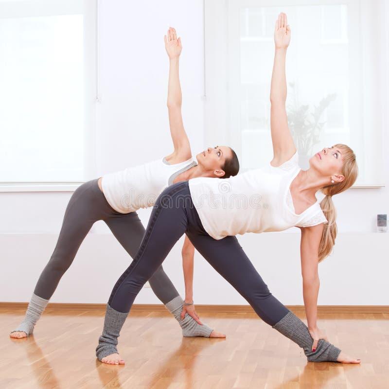 Frauen, die Yogaübung an der Gymnastik tun lizenzfreie stockfotografie